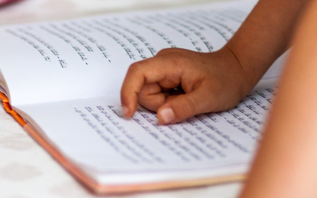 kid's hand pointing on Devanagari script book